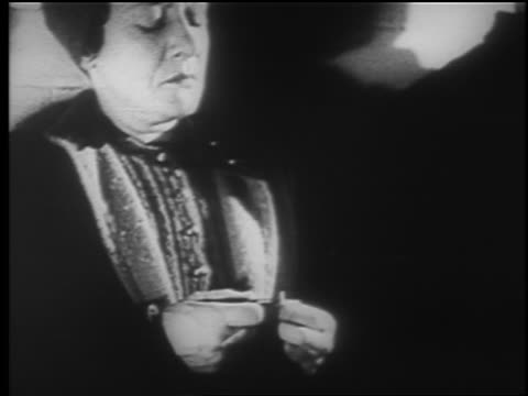 vidéos et rushes de b/w 1940 close up middle aged woman looks down at hands in air raid shelter / london blitz / educational - 1940