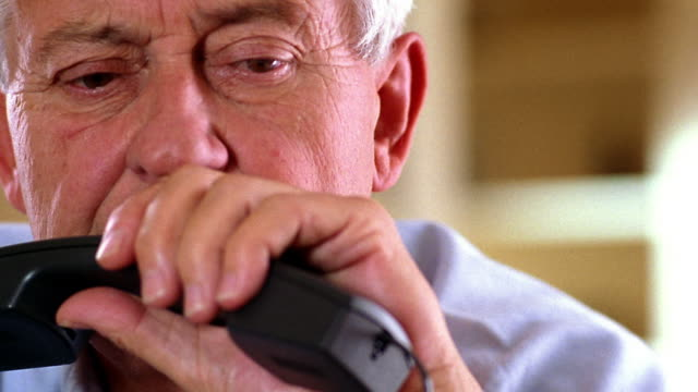 close up middle age/mature man holding telephone receiver looking worried - mature adult video stock e b–roll