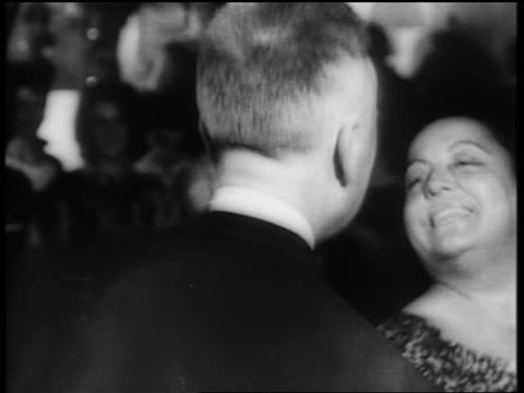 B/W 1961 close up middle-aged couple Twisting on dance floor as crowd looks on / newsreel