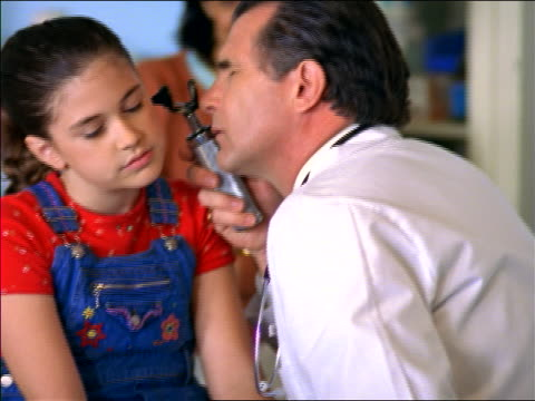 close up middle-aged male doctor checking ears of girl in overalls with otoscope / mother in background