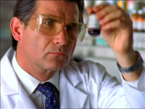vídeos y material grabado en eventos de stock de close up middle-aged male scientist with goggles shaking + looking at vial of fluid in lab - only mature men