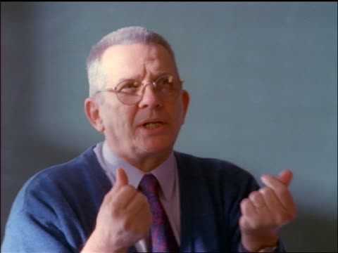 close up middle-aged male teacher with eyeglasses talking + gesturing with fingers - einzelner mann über 40 stock-videos und b-roll-filmmaterial