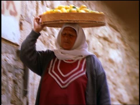 vídeos de stock, filmes e b-roll de close up middle-aged muslim woman carrying basket of food on head walking toward camera / jerusalem - só uma mulher madura
