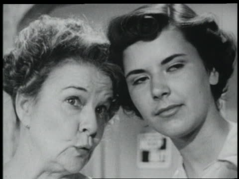 b/w 1951 close up middle-aged woman + young woman gossiping while looking off screen - flüstern stock-videos und b-roll-filmmaterial