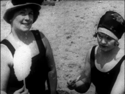 B/W 1925 close up middle-aged + young woman in swimsuits + hats waving fans on beach / newsreel