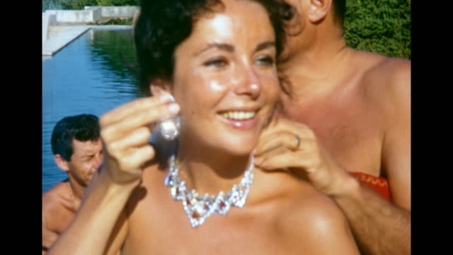 close up mike todd putting jeweled necklace on elizabeth taylor as she holds earring up to her ear - necklace stock videos & royalty-free footage