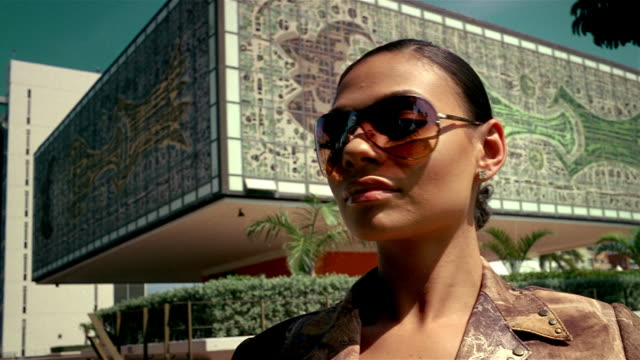 Close up model wearing sunglasses posing in front of building with mosaic design