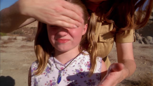 Close up mother applying sunscreen to young girl's face outdoors