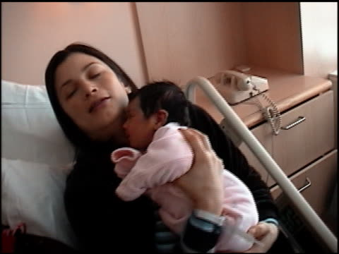 Close up mother holding newborn baby in hospital bed / bouncing baby up and down