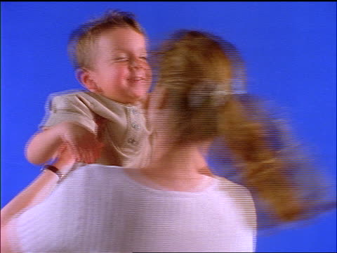 close up mother holding small boy above her head spinning in front of blue screen - murmursofearth点の映像素材/bロール