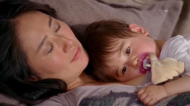 vídeos y material grabado en eventos de stock de close up mother resting with baby on couch or bed / baby sucking pacifier and looking at cam - mamar