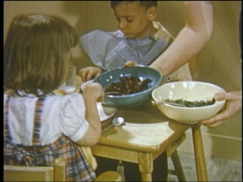 1952 close up mother serving bowls of vegetables to 2 young children sitting at kiddie table - 1952 stock videos & royalty-free footage