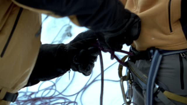Close up mountain climber tying rope on partner's harness / Mount Washington, New Hampshire