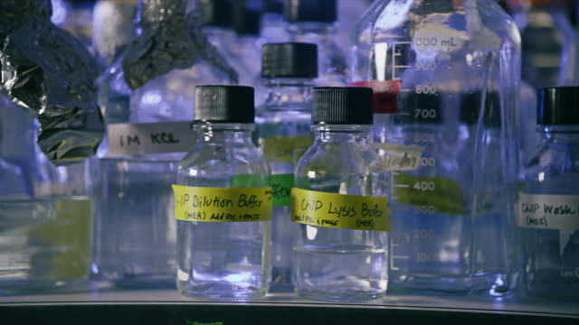 close up, multitude of glass bottles with chemical solutions in a medical scientific laboratory - 英字点の映像素材/bロール