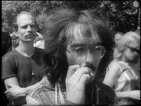 vídeos de stock e filmes b-roll de b/w 1967 close up mustached male hippie in eyeglasses smoking joint outdoors at bein / london / newsreel - hippie