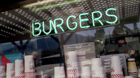 close up neon 'burgers' sign in window of fast food restaurant - fast food stock videos & royalty-free footage