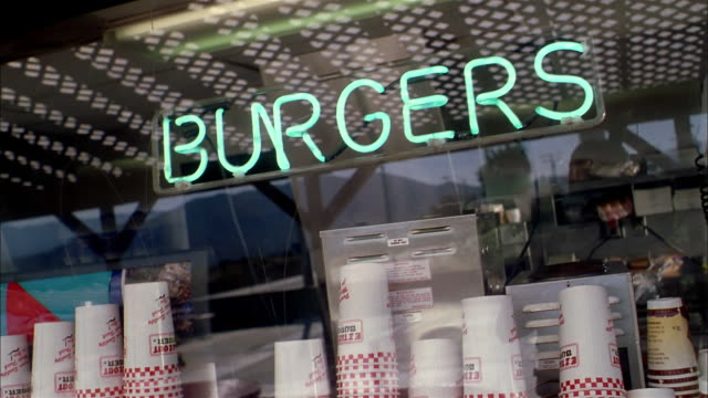 close up neon 'burgers' sign in window of fast food restaurant - ファーストフード点の映像素材/bロール