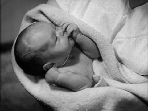 vidéos et rushes de b/w 1948 close up newborn baby being held / michigan / medical industrial - nouvelle vie