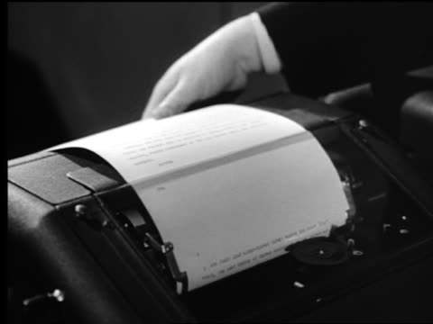 b/w close up news teletype machine printing out message / man's hand ripping off printed page - 破れている点の映像素材/bロール
