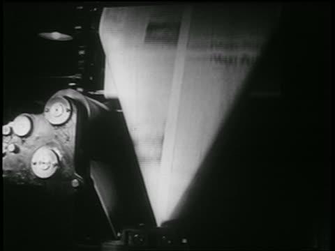b/w 1939 close up newspaper folding thru machine in printing plant / documentary - 1930 1939 video stock e b–roll