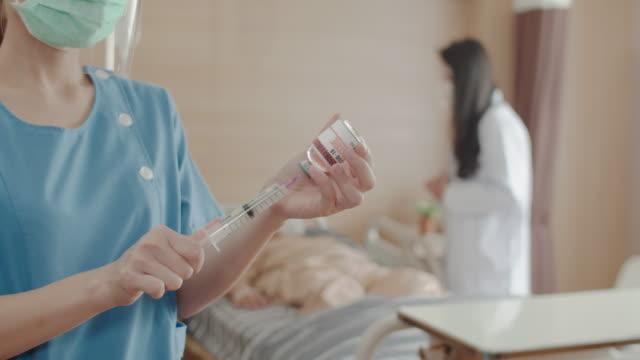 stockvideo's en b-roll-footage met close-up nurse handen en spuiten worden corona virus gevaccineerd aan patiënten in het ziekenhuis - medicijnflesje