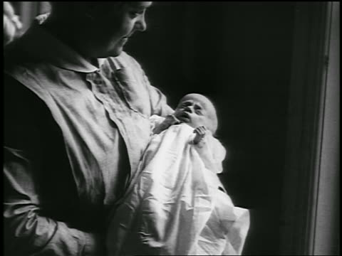 stockvideo's en b-roll-footage met b/w 1920 close up nurse holding newborn baby / detroit, michigan / newsreel - 1920