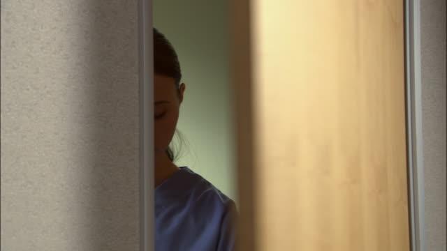vídeos de stock, filmes e b-roll de close up nurse opening door and reading name off of clipboard - falando
