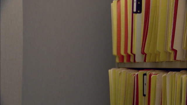 close up nurse retrieving file from filing room in doctor's office - medical record stock videos & royalty-free footage