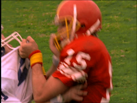 close up of 2 football players fighting / others join in / Referee breaks it up