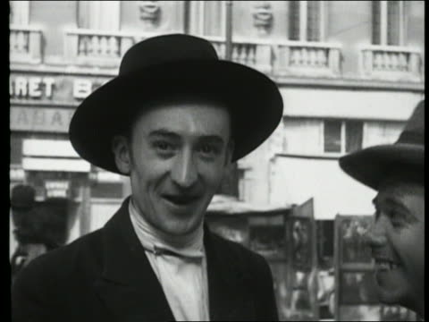 B/W 1927 close up of 2 men in hats smiling + laughing / Paris, France