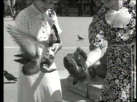b/w 1930 close up of 2 women feeding pigeons on st. mark's square / venice, italy - 1930 video stock e b–roll