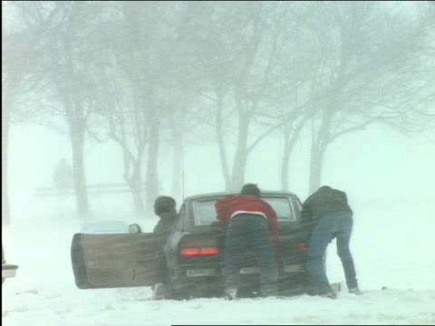 vidéos et rushes de close up of 3 men trying to push car stuck in snowstorm - panne de voiture