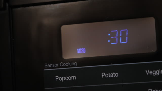 close up of 30 seconds entered and counting down cooking time on a black digital display microwave - microwave stock videos & royalty-free footage