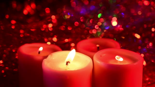 close up of 4 candles with a lit flame which are blown. christmas decoration in background. - 宗教上のシンボル点の映像素材/bロール