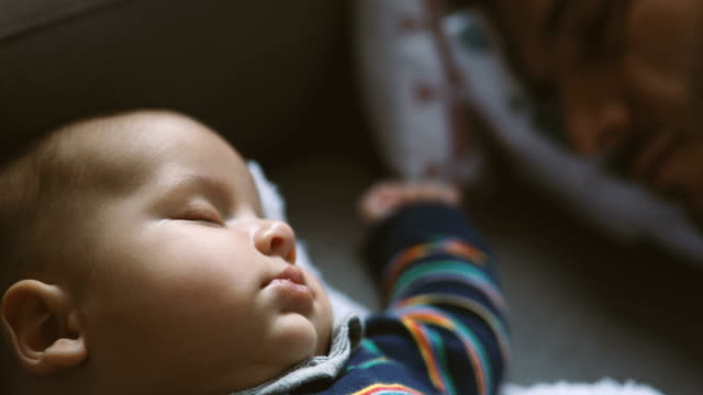 close up of a baby sleeping on a sofa with dad - sleeping stock videos & royalty-free footage