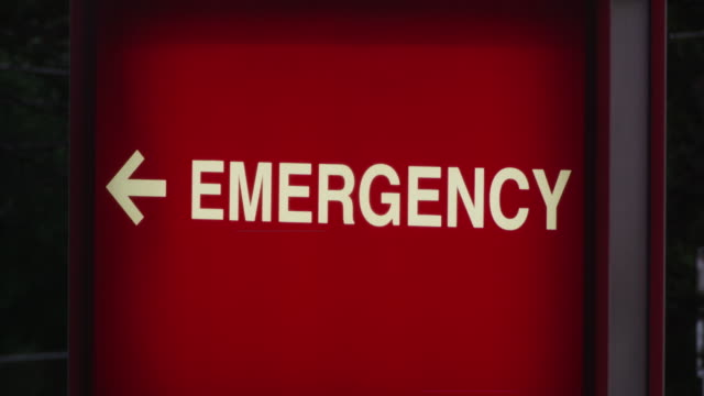 Close up of a backlit hospital 'Emergency' sign is eclipsed by an ambulance with lights flashing at night.