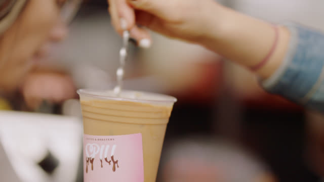 close up of a barista stirring iced coffee in a plastic disposable cup with a stirring rod - stirring stock videos & royalty-free footage
