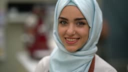 Close up of a beautiful muslim business owner of a restaurant looking at camera smiling