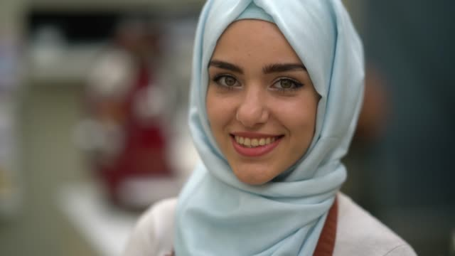 close up of a beautiful muslim business owner of a restaurant looking at camera smiling - televisione a ultra alta definizione video stock e b–roll