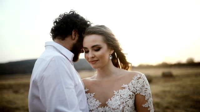 Cerca de un hermoso recién casado abrazando en el Prado en una puesta de sol