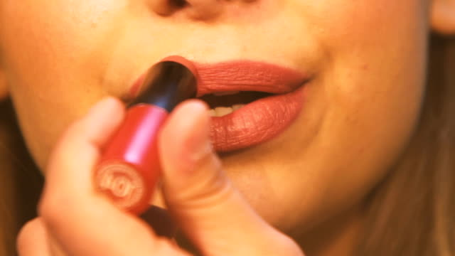 Close up of a beautiful young woman is in make-up in front of the mirror with lipstick