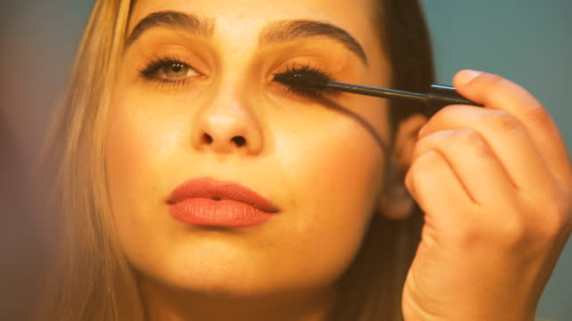 close up of a beautiful young woman is in make-up in front of the mirror with eyelash curler - mascara stock videos & royalty-free footage