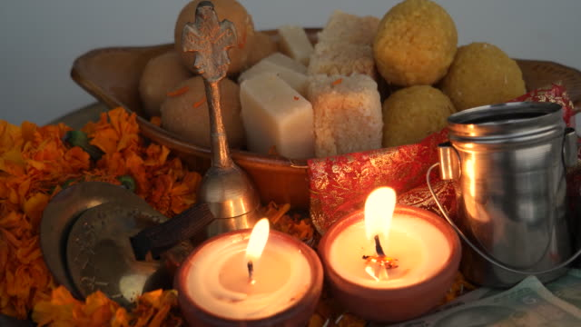 close up of a beautifully decorated hindu puja or pooja thali to worship with currency notes, fresh flowers, sweets, burning diyas, bell splash cymbals in a brass plate - sweet food stock videos & royalty-free footage
