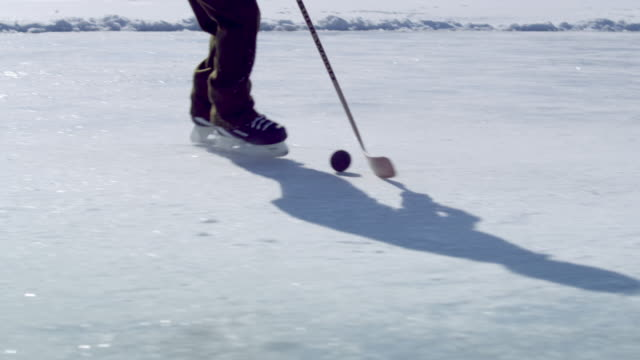 close up of a boy practicing hockey at an outdoor ice rink. - one teenage boy only stock videos & royalty-free footage