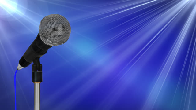 Close up of a cardioid dynamic ball head microphone on a stand turning against a blue background with light flares