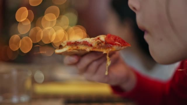close up of a cheesy slice of pizza ending in the mouth - parte de una serie video stock e b–roll