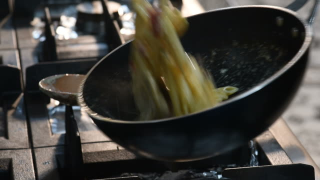 close up of a chef sauteing pasta in a pan - saute stock videos and b-roll footage