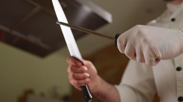 vídeos de stock, filmes e b-roll de feche acima de um chef afiando sua faca. - afiado