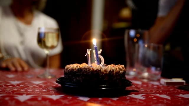 vidéos et rushes de close up of a chocolate cake with burning candles on a dining table - anniversaire d'un évènement