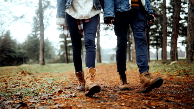 Close up of a couple walking in slow motion in a forest